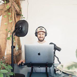 man in black headphones and macbook